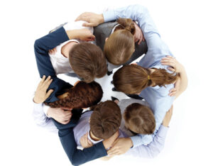 Above view of several business partners nodding heads and embracing each other standing in circle