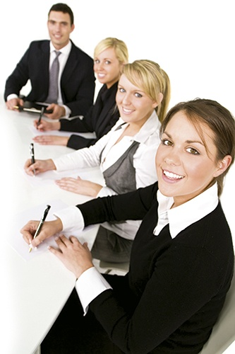 A smiling businesswoman and her three colleagues out of focus behind her taking part in a happy business meeting